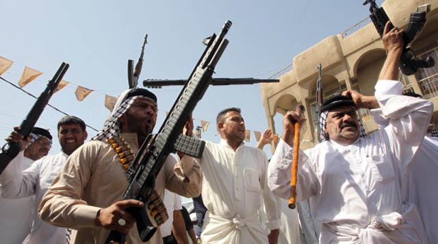 Iraqi tribes men carry their weapons as they gather, volunteering to fight along side the Iraqi security forces against Jihadist militants, on June 14, 2014, in the capital Baghdad. Leading Shiite cleric Grand Ayatollah Ali al-Sistani urged Iraqis on June 13 to take up arms against Sunni militants marching on Baghdad, as thousands volunteered to bolster the capital's defences. AFP PHOTO/ALI AL-SAADI        (Photo credit should read ALI AL-SAADI/AFP/Getty Images)