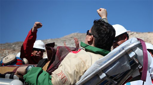 In this photo released by the Chilean government, Edison Pena, gestures to Chile's Mining Minister Laurence Golborne, left, as he is carried on a stretcher after being rescued at the San Jose mine, near Copiapo, Chile, Wednesday, Oct. 13, 2010. Pena was the twelfth of 33 miners rescued from the San Jose mine after more than 2 months trapped underground. (AP Photo/Hugo Infante, Chilean government)